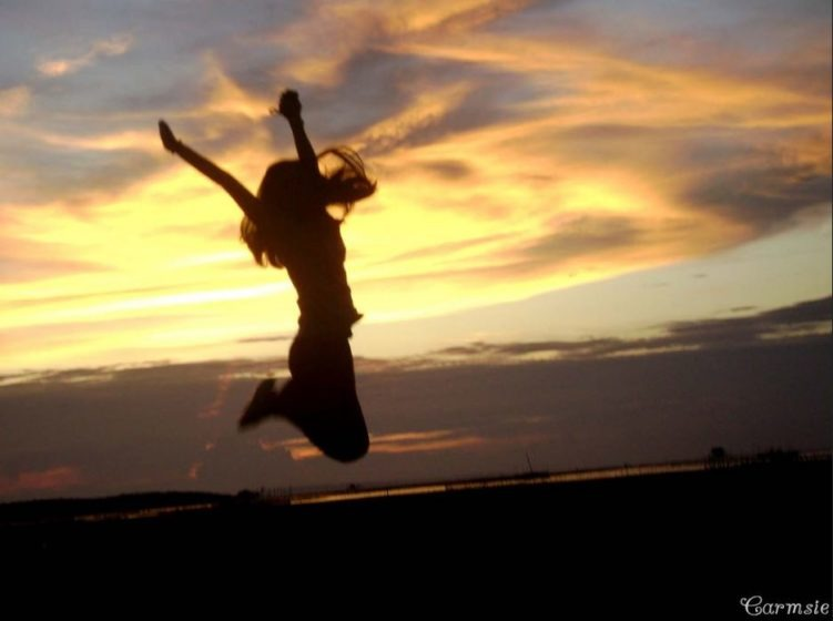 You can change your life for the better using the power of positivity. Photo of woman jumping for joy at sunrise.