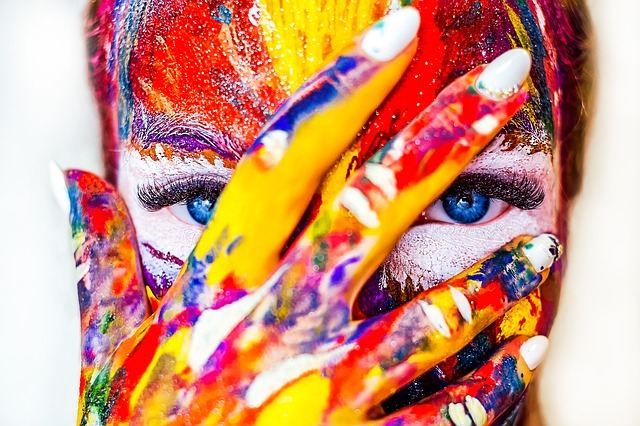 a creative woman with paint on her hands and face