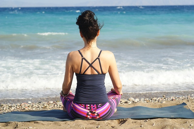 a woman meditating on a beach, one of the brain tricks
