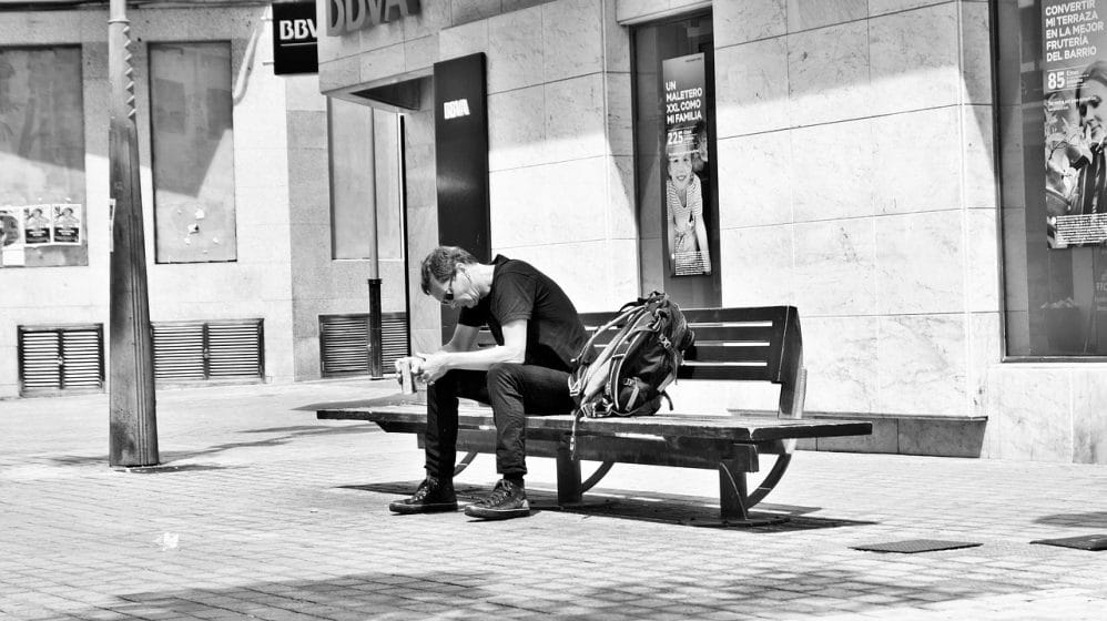 black and white photo of a man sitting on a bench