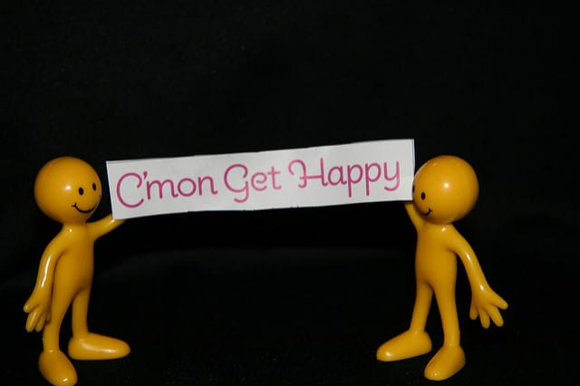 two small human figurine with happy faces holding banner saying, 'c'mon get happy'