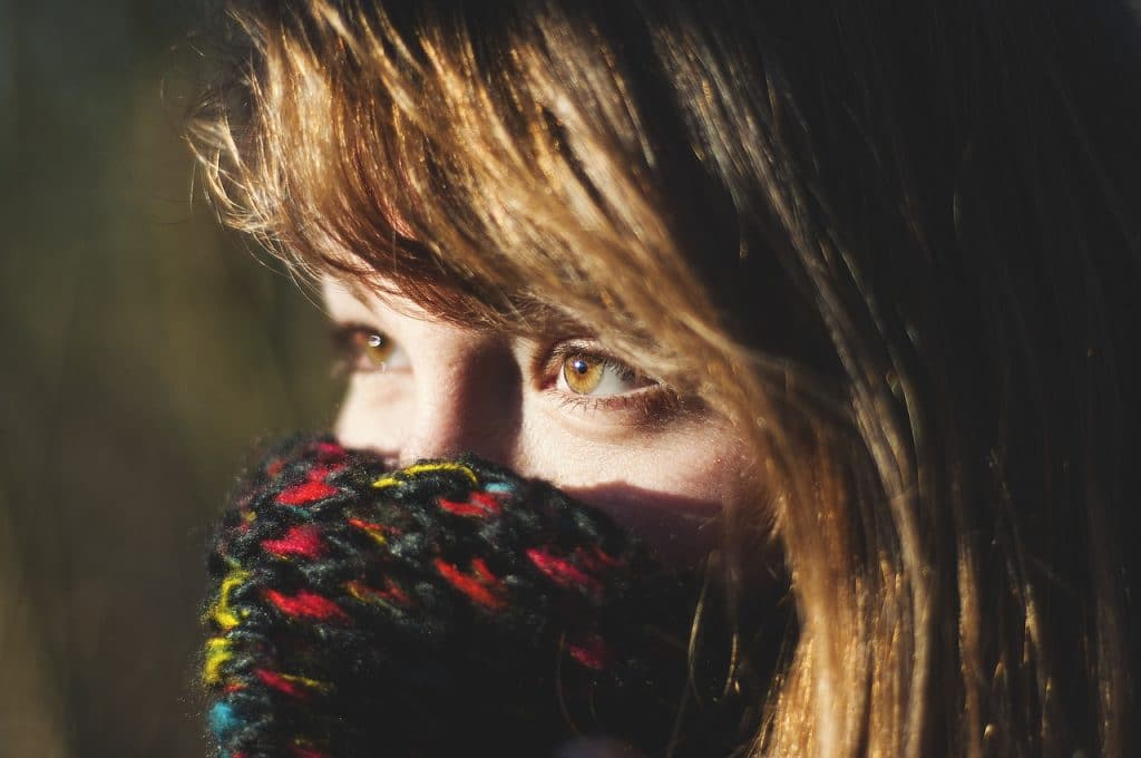 close-up photo of a woman with cover in her mouth and nose and with her eyes focusing on an object in her left