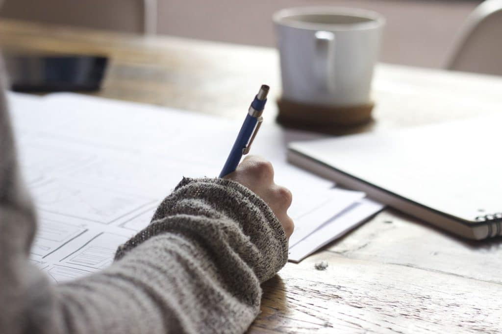 close-up photo of a person writing on paper the list that stress her out